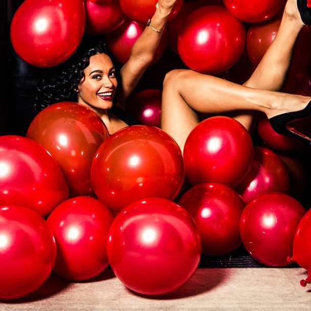 A woman sitting in a pile of red balloons
