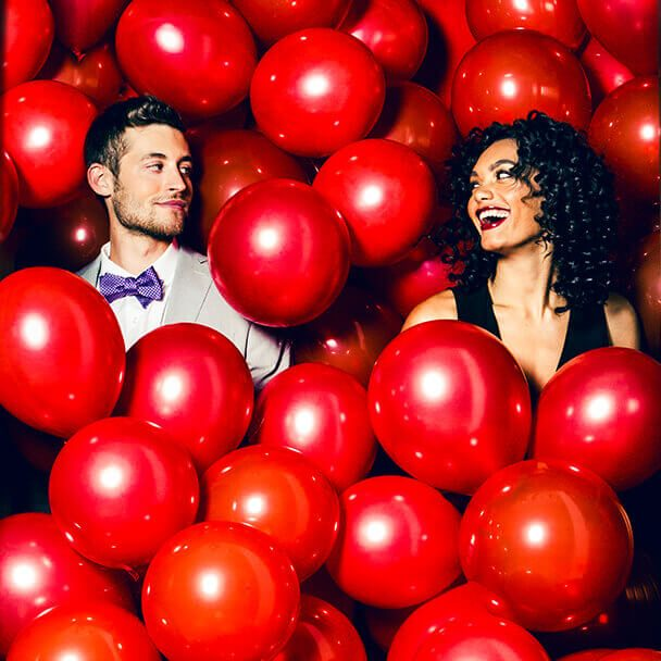 Couple standing in red balloons