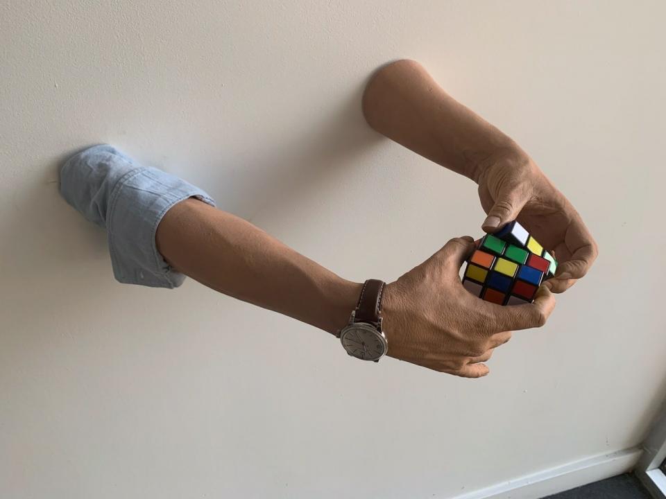 Art piece at Virgin Hotels Dallas of Richard Branson's arm working a Rubix Cube